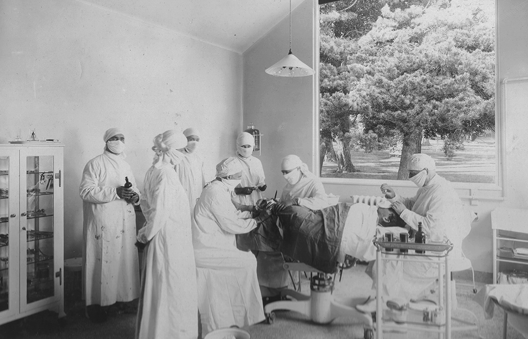 Nurses and doctors operate on a patient