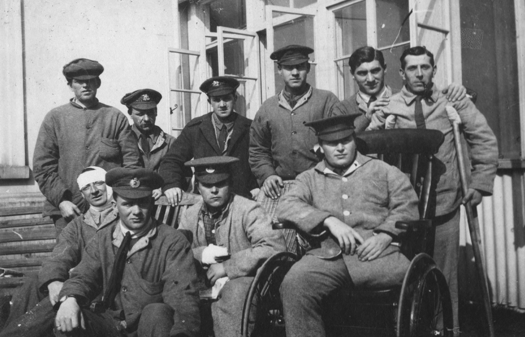 A group of injured soldiers including some with wheelchairs, crutches.